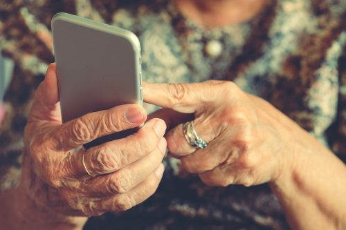 Close up of an older woman's hands using a mobile phone.